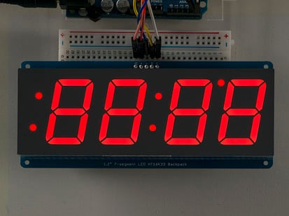 Huge red 7-segment clock display soldered to backpack with all segments lit