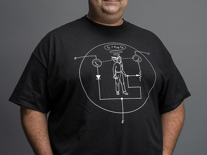 Man wearing black t-shirt with white NPN transistor diagram with a man inside the diagram