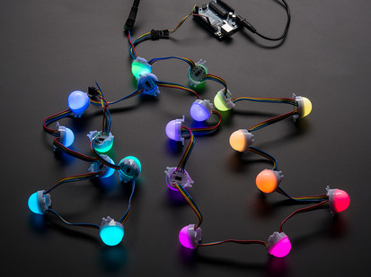 Cluster of many lit up LED pixel hemispheres on wire strand, rainbow colored