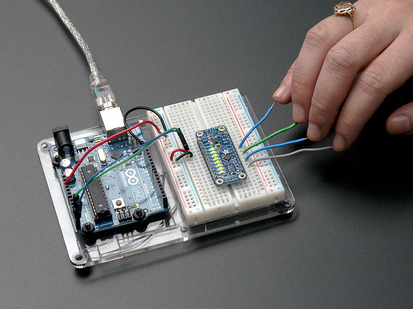 Capacitive Touch Sensor Breakout on breadboard with hand touching many attached wires