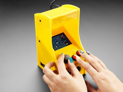 Two hands playing Cupcade with very small pacman game on display