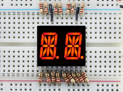 Red Dual Alphanumeric Display module wired to breadboard, all segments lit