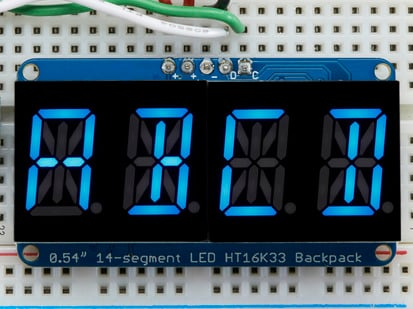 "Assembled Quad Alphanumeric Display with blue display showing ""ABCD"""
