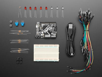 Budget pack kit contents, microcontroller board, breadboard, wires, and parts.