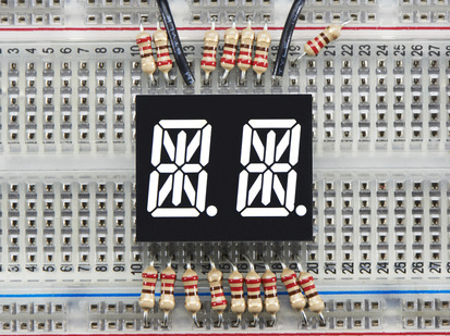 White Dual Alphanumeric Display module wired to breadboard, all segments lit