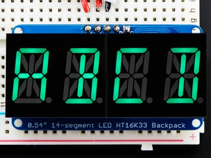 "Assembled Quad Alphanumeric Display with green display showing ""ABCD"""