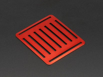 Angled shot of slotted red aluminum sheet.
