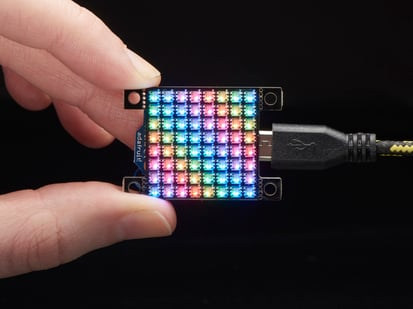 Hand holding small Adafruit DotStar High Density 8x8 Grid - 64 RGB LED Pixel Matrix
