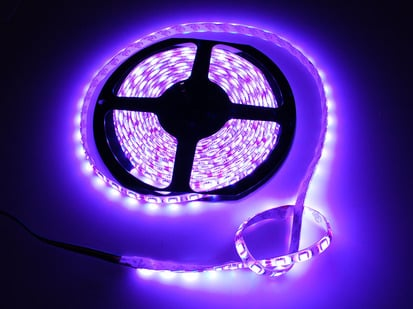 Spool of flexible LED strip lit up purple