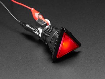 Angled shot of a red triangle illuminated LED pushbutton.