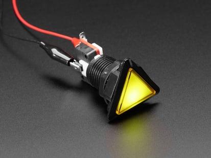 Angled shot of a yellow triangle illuminated LED pushbutton.