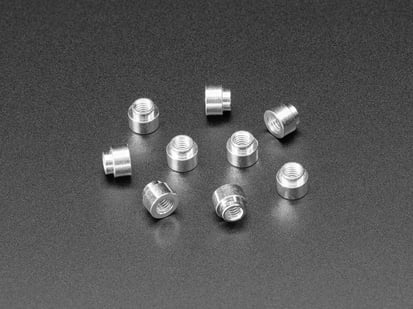 Angled shot of ten 3mm tall M3 standoff nuts.