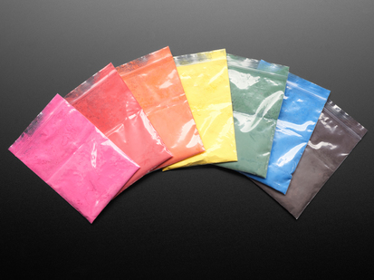 Angled shot of six clear baggies fanned out. The bags contain powder paint pigments separated by color: red, orange, yellow, green, blue, black, and pink.