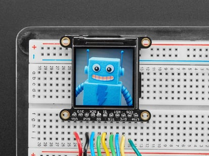 TFT breakout wired up on breadboard, showing colorful image of friendly robot