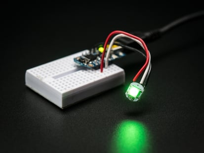 Glowing NeoPixel Mini Button PCB wired up to a microcontroller