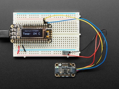 Adafruit PCT2075 Temperature Sensor with STEMMA QT / Qwiic cable plugged into a Feather showing the temperature