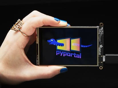 "Hand holding PyPortal Titano development board with SAMD51, ESP32 Wifi, and 3.5"" touchscreen TFT display."