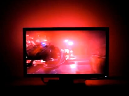 Large flatscreen TV with red-tinted scene and red LEDs lighting wall behind it.