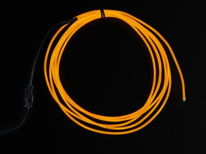 Coil of lit EL wire in orange