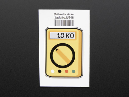 Rectangular sticker in the shape of yellow multimeter with dial, and a grey screen reading 1.0 kilohms. Mounted on white paper with barcode.