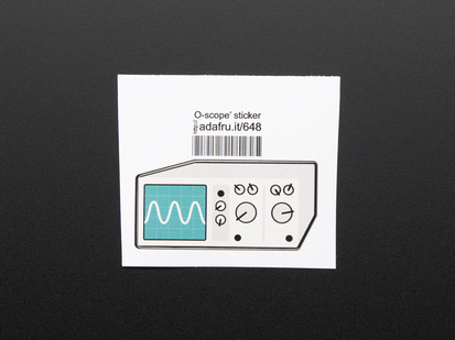 Sticker in the shape of analog oscilloscope in grey with turquoise screen showing sine wave. Mounted on white paper with barcode.