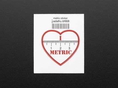 Heart shaped sticker with the numbers 1, 2, 3 and the markings of a ruler in black over a white background. The words I and METRIC in red above and below the ruler. The sticker is trimmed in red and mounted on white paper with barcode