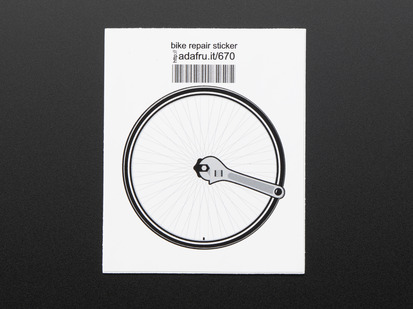 Circular sticker of a bicycle wheel in black and grey with a wrench turning the central nut, over a white background. Mounted on white paper with barcode.