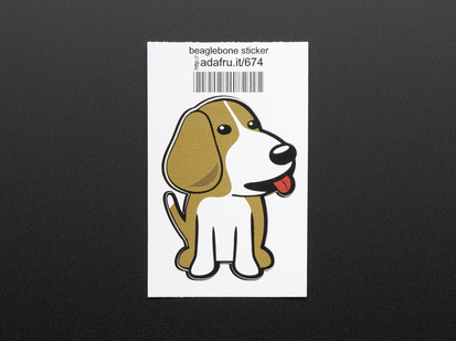 Sticker in the shape of sitting BeagleBone dog logo. Dog is brown and white with red detail for tongue. Mounted on white paper with barcode.