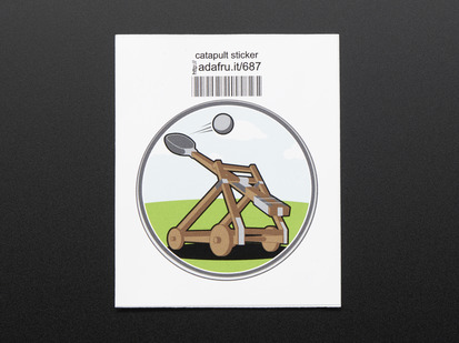 Circular sticker with brown catapult mid-fling, over an abstracted blue sky and green grass background. Sticker is trimmed in grey and mounted on white paper with barcode.