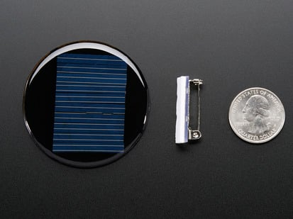 Round solar panel next to lapel pin and quarter