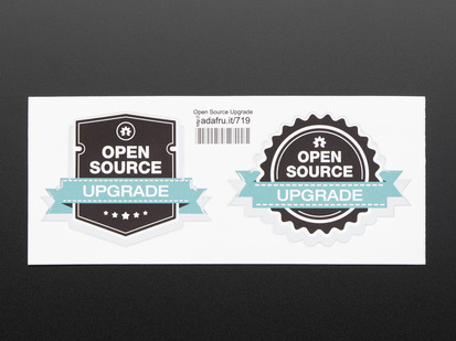"photograph of two black stickers, one shield shaped, the other gear shaped, with white lettering reading ""open source"" with a turquoise banner running across each reading ""upgrade"" both stickers are mounted on white paper with barcode."
