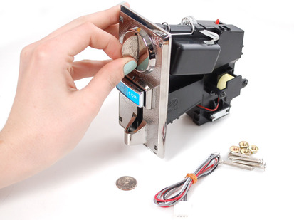 Hand inserting quarter into coin mechanism slot with hardware and wires nearby