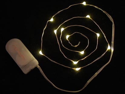 Coil of thin flexible wire with lit up embedded LED 'fairy' lights attached to battery holder