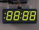 Huge green 7-segment clock display soldered to backpack with all segments lit