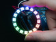Hand holding NeoPixel Ring with 16 x 5050 RGB LED, lit up rainbow