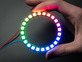 Hand holding NeoPixel Ring with 24 x 5050 RGB LED, lit up rainbow