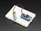 Adafruit LiIon/LiPoly Backpack soldered onto a Pro Trinket, plugged into a solderless breadboard.