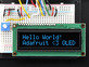 """Wired up 16x2 OLED with blue on black text """"Hello World! Adafruit <3 OLED"""""""