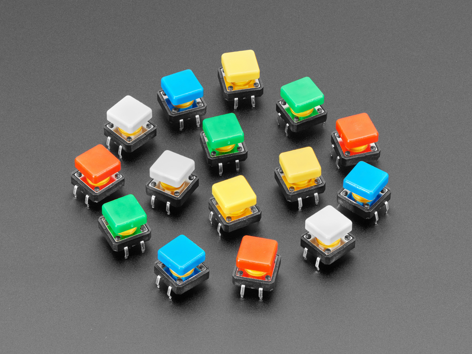 Top-down shot of 15 colorful square tactile button switches in green, yellow, red, blue, and white.
