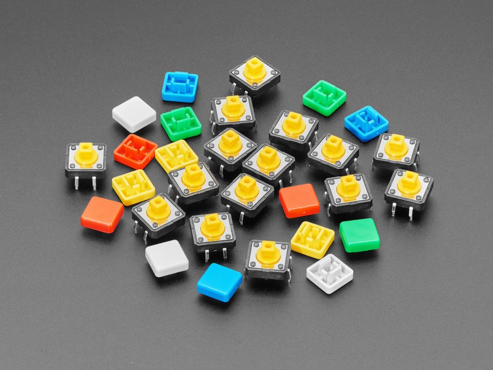 Pile of 15 colorful square tactile button switches in green, yellow, red, blue, and white.