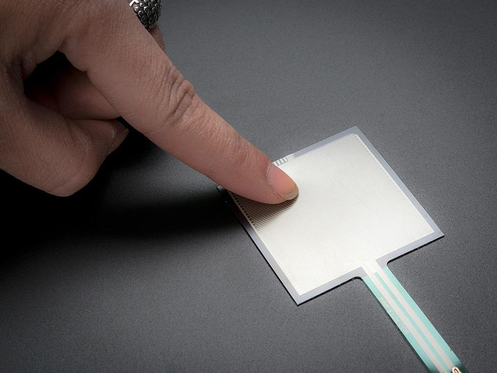 Finger pressing down on square force-sensitive sensor