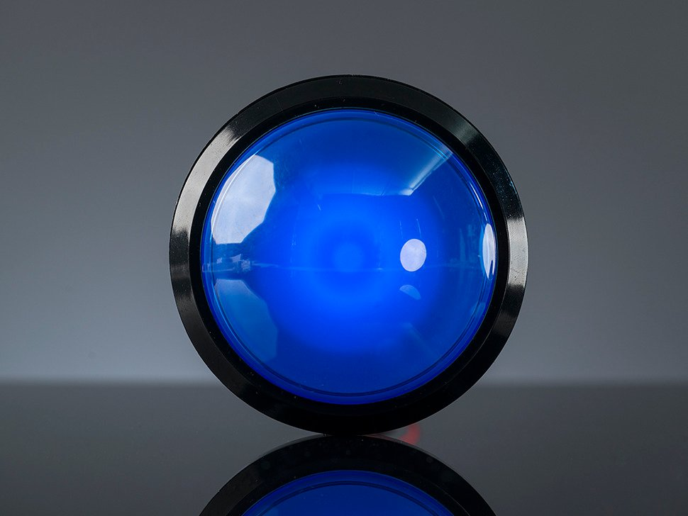 Head-on shot of illuminated massive blue 100mm arcade button.