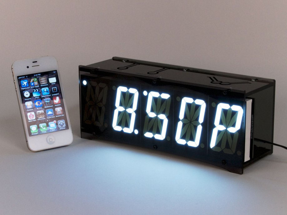 """Front of clock showing """"8:50 P"""" text on display next to iPhone"""