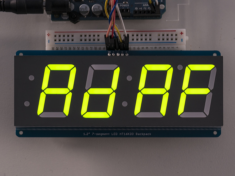 "Huge green 7-segment clock display soldered to backpack showing ""AdAF"" on display"