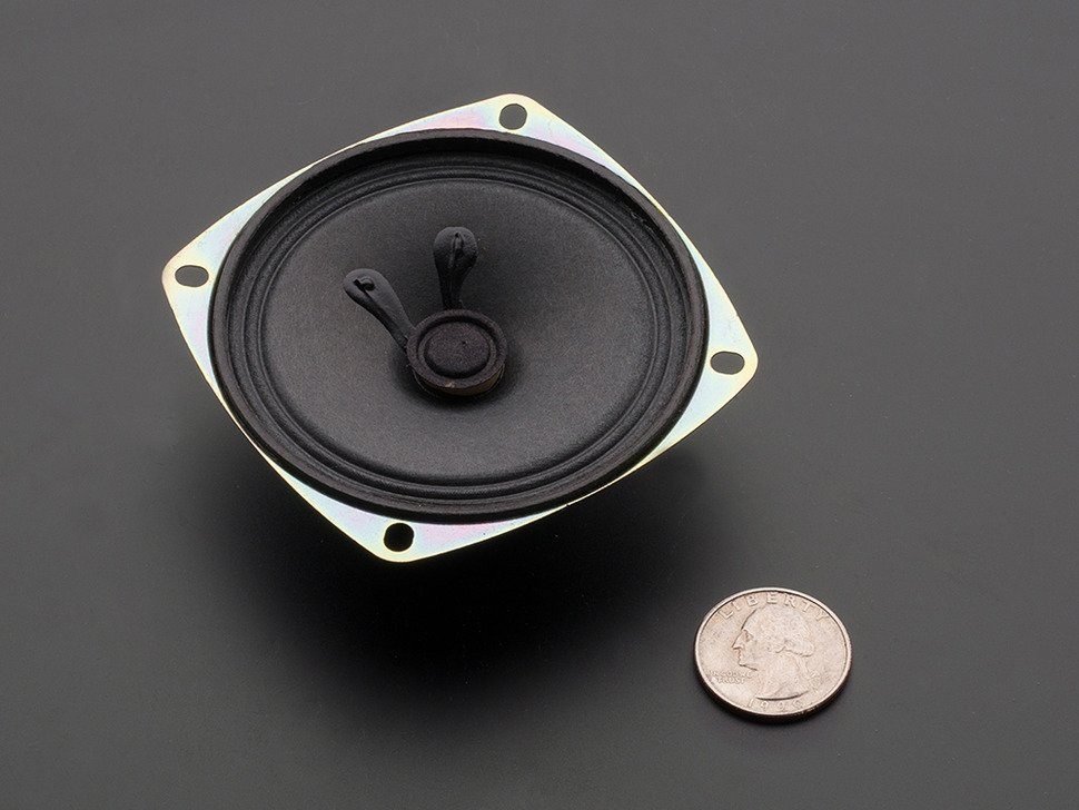 Speaker is face up next to quarter for size reference