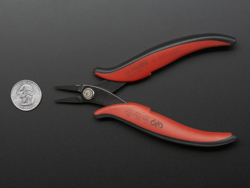 Red and black needle-nose pliers next to quarter
