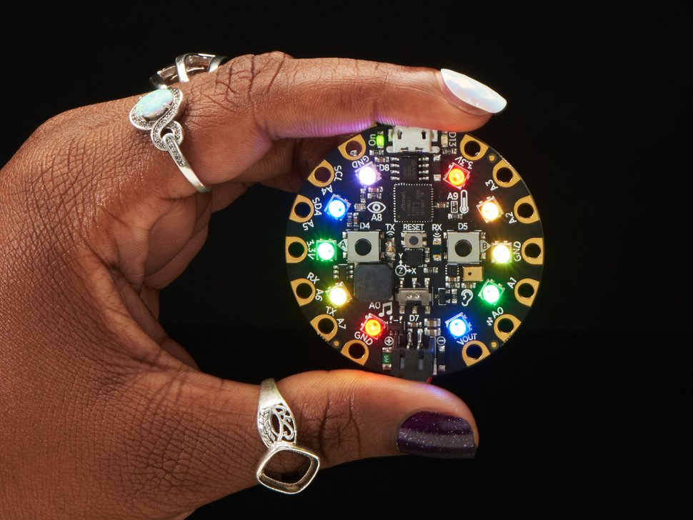 Hand holding a rainbow-glowing circuit playground