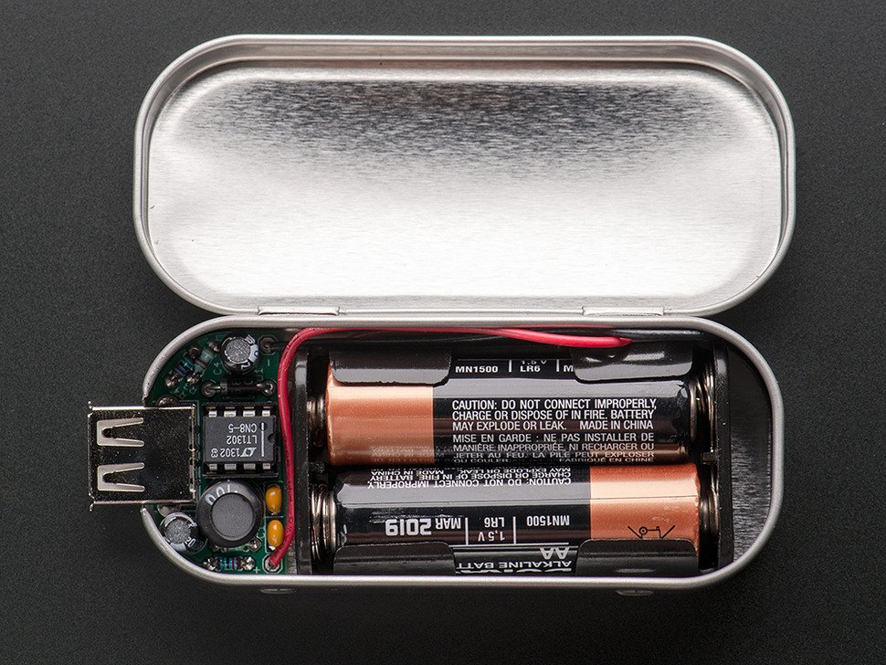 Assembled MintyBoost kit in mint tin with top open showing two AA batteries.