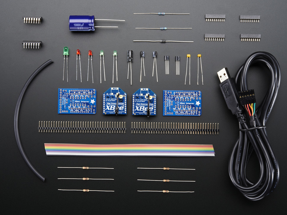 Collection of doubled-up loose components in kit: PCBs, XBees, connectors, ribbon cable, and other parts.