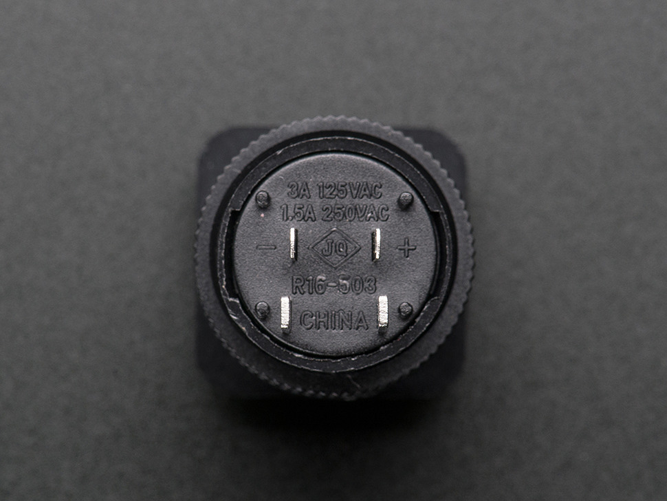 Back of pushbutton featuring four leads.